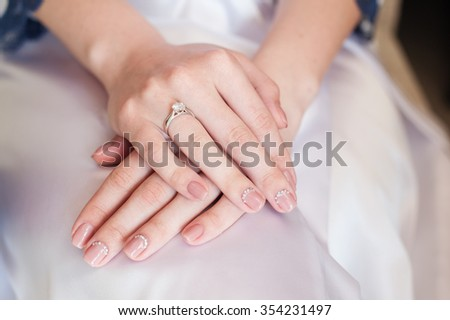 Bride hand with manicure on wedding dress. - stock photo