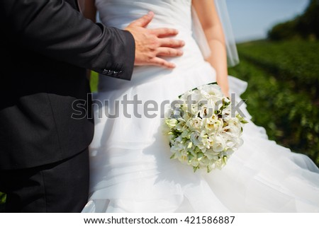 Bride hold groom by the hand and wedding bouquet. Focus on wedding flower bouquet. Crop by chest and legs. Bride in wedding dress, groom wears classic clothes. - stock photo