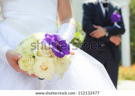 Bride hold her wedding bouquet made from white roses with lilac orchid - stock photo