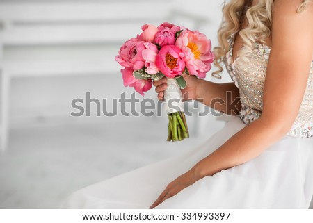 bride holding beautiful wedding bouquet of pink peonies - stock photo