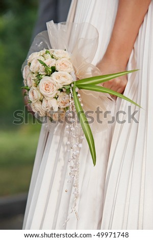 Bride holding bouquet of flowers, outdoor shot - stock photo