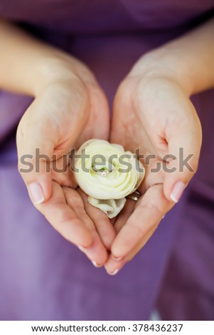 Bride holding flower and engagement ring - stock photo