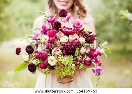 Bride holding purple boho bouquet - stock photo