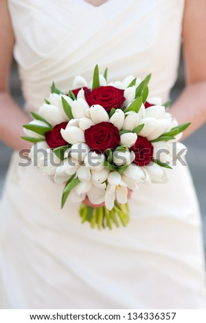 bride holding red rose and white tulip wedding bouquet - stock photo
