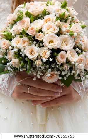 Bride holding wedding bouquet of roses in his hands - stock photo