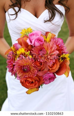 Bride Holding Wedding Bouquet with Orange and Pink Flowers - stock photo