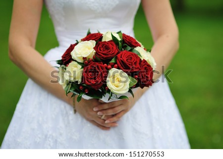 Bride holding wedding flower bouquet of red and white roses - stock photo