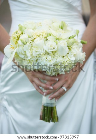 Bride holding wedding flower bouquet of white roses - stock photo