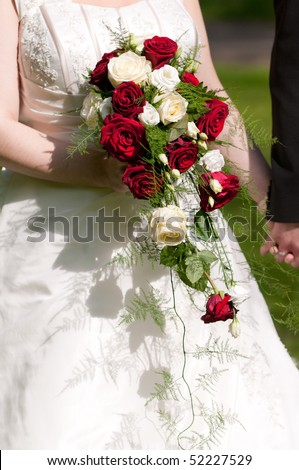 Bride holds Brautrauss with roses in hand - stock photo