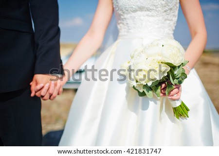 Bride holds groom by the hand and wedding bouquet. Focus on wedding flower bouquet. Bride in wedding dress, groom wears classic clothes. - stock photo