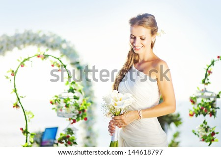 bride in a flourish arch on the wedding venue, bali - stock photo