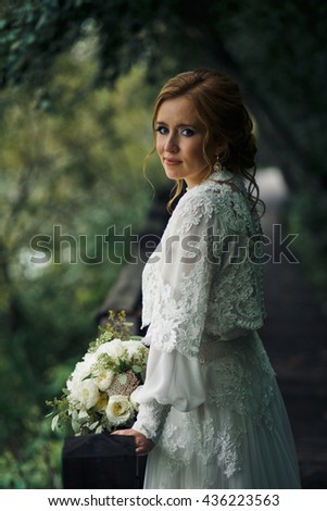 Bride in a perfect dress decorated with laces poses in the dark garden - stock photo