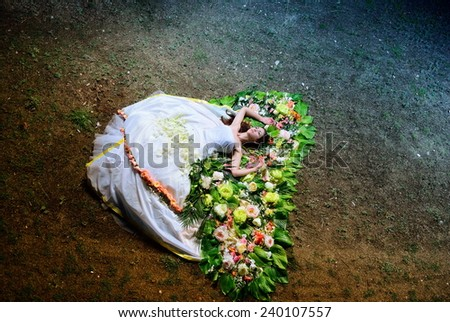 bride in a wedding dress is sleeping on the ground - stock photo