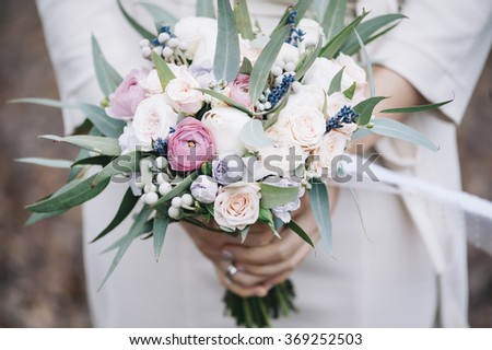 Bride in a white dress holding a beautiful wedding bouquet in her hands - stock photo
