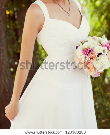 Bride in a white dress in summer green park with a bouquet in hand - stock photo