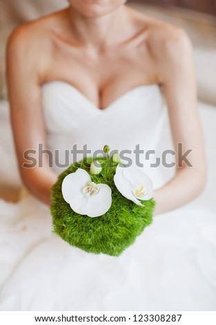 Bride in a white dress with a bouquet in hand - stock photo