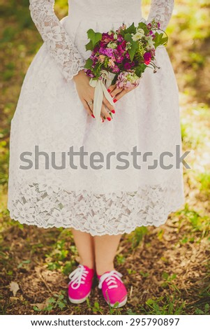 bride in pink sneakers, Wedding bouquet with bright pink flowers in the hands of the bride - stock photo