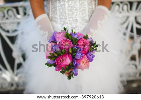 Bride in white dress and gloves holding wedding bouquet made of pink peonies - stock photo