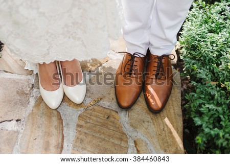 bride in white shoes and groom in brown shoes stand side by side - stock photo