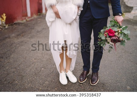 bride in white sport shoes and groom in vinous shoes stand side by side, groom holds a wedding bouquet - stock photo