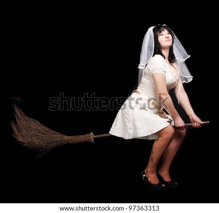 bride in white wedding dress on a broom. Girl with big breasts - stock photo