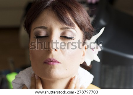 Bride is getting professional make up for her wedding day,almost done feeling relaxed. - stock photo
