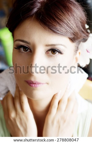 Bride is getting professional make up for her wedding day, finish. - stock photo