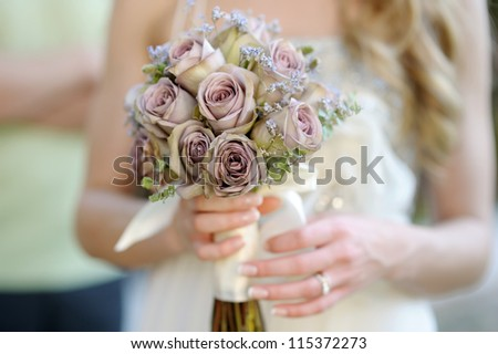 Bride is holding a beautiful wedding bouquet - stock photo