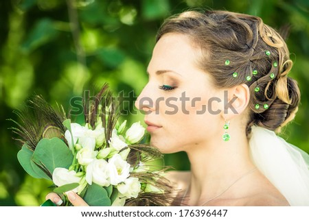 Bride is holding a bouquet near her cheek - stock photo