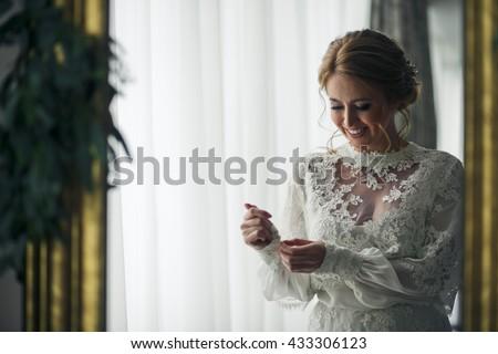 Bride looks fabulous adjusting long sleeves on a wedding dress - stock photo
