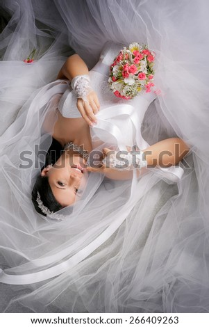 Bride lying next to the veil with bouquet on a white background - stock photo