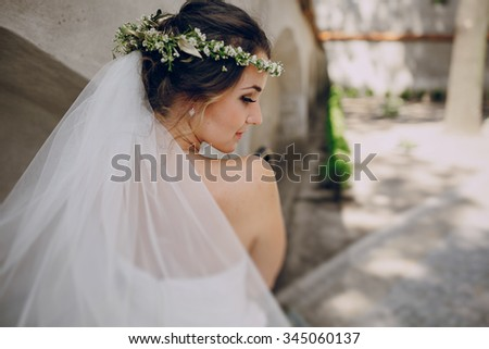 bride poses for photos in wedding dress and wreath - stock photo