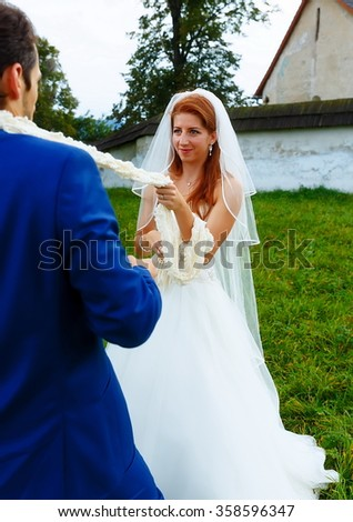 bride pulling her groom to her with a rope - funny wedding concept. - stock photo