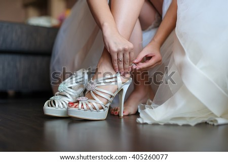 Bride puts on a shoes to a foot standing in a room on a brown floor. Woman buttons white shoe. Mirror surface of the floor. Beautiful wedding white dress. - stock photo