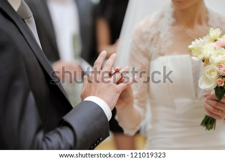 bride puts wedding ring on groom's finger - stock photo