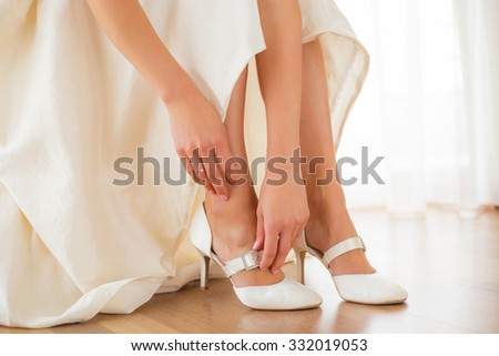 Bride putting on her white shoes  - stock photo