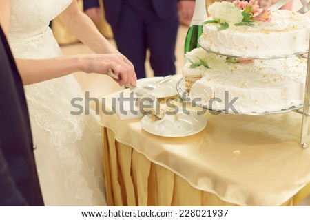 bride putting slices of wedding cake on plate - stock photo