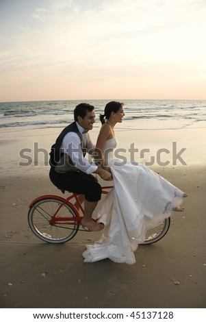 Bride rides the handle bars of a bicycle being driven by her groom on the beach. Vertical shot. - stock photo