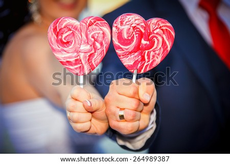 bride's and groom hands holds heart shaped lollipop - stock photo