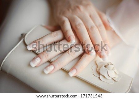 bride's arms with manicure holding a wedding purse - stock photo