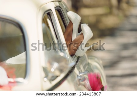 bride's feet in white wedding shoes in car window - stock photo