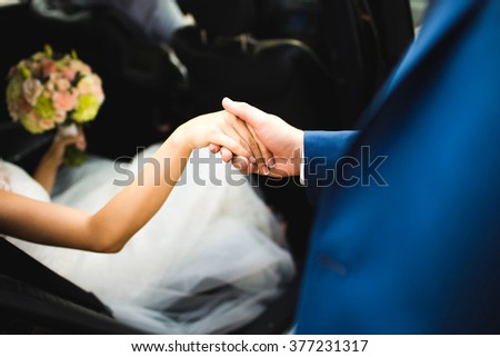bride's hand and the hand of the groom while getting out of the car or automobile. True affection. Close up view. - stock photo