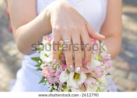 Bride's hand with a ring on a bouquet closeup - stock photo