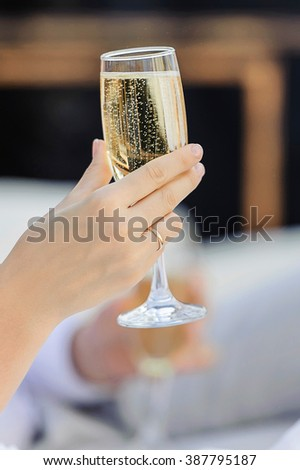 Bride's hand with a wedding ring holding a glass of champagne with bubbles. - stock photo