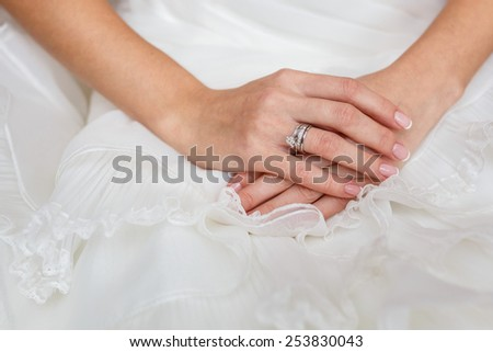 bride's Hand with Diamond ring on white dress - stock photo