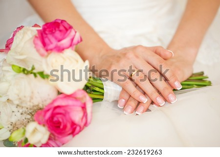 Bride's hands with wedding flowers. - stock photo