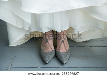 Bride's shoes under white wedding dress, on rustic wooden floor - stock photo
