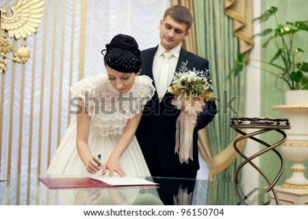 Bride signing her wedding license. Groom stands near - stock photo