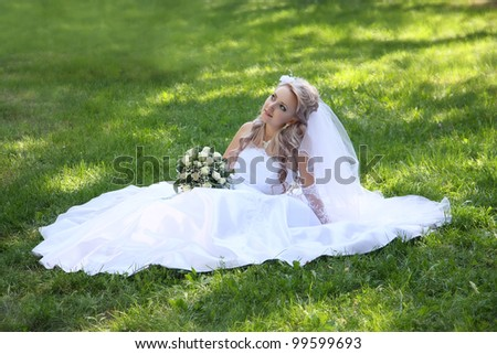 bride sits on  grass. Summer.  sunny day. - stock photo