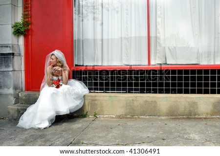 Bride sits on steps of downtown alley.  Bright red door and black tile accent shop behind her.  Matching rose bouquet lays in her lap.  Her hands are laced and she is gazing down the street. - stock photo